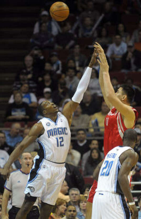 Yao Ming shoots over Magic center Dwight Howard in the first half. Photo: Phelan M. Ebenhack, AP