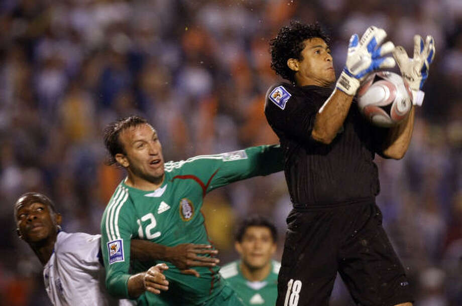El portero de Honduras Noel Eduardo Valladares ataja un pelotazo, mientras el jugador mexicano Vicente Matías Vuoso, quien estaba detrás, mira antentamente la jugada. Photo: Gregory Bull, AP