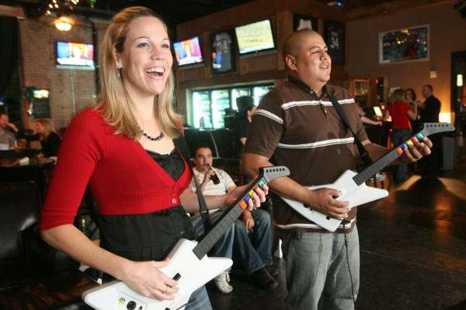 Kristin Finan and Roland Silva jam out on the Guitar Hero game at Lucky's Pub. Photo: Bill Olive, For The Chronicle