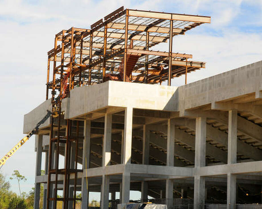 Workers work on the press box and suites high above the football stadium at the new athletic complex behind the Portofino Shopping Center. Photo: David Hopper, For The Chronicle
