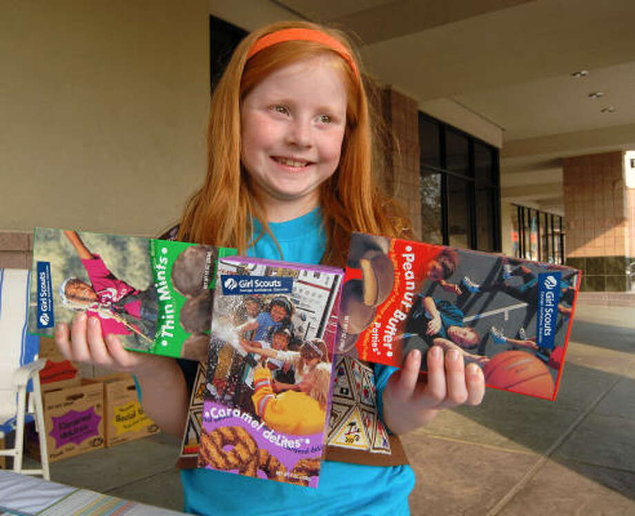 Lauren Diggins of Brownie Troop 13094 holds up Girl Scout cookies her troop is selling at the Kroger store on Woodlands Parkway. Many of the 2,650 Girl Scouts in the 250 troops around Montgomery County are busy setting up cookie booths at local businesses to meet their sales goals for this year's cookie campaign which ends March 25. Photo: David Hopper, For The Chronicle