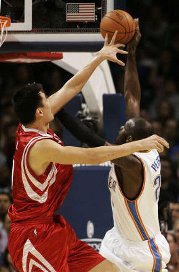Rockets center Yao Ming blocks a shot by Oklahoma City Thunder center Johan Petro in the first quarter on Monday. Photo: Sue Ogrocki, AP