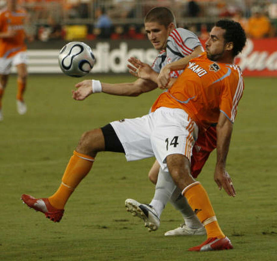 Dwayne De Rosario and the Dynamo have made it next to impossible for players like Toronto FC's Carl Robinson to get scoring chances lately. Photo: Kevin Fujii, Chronicle