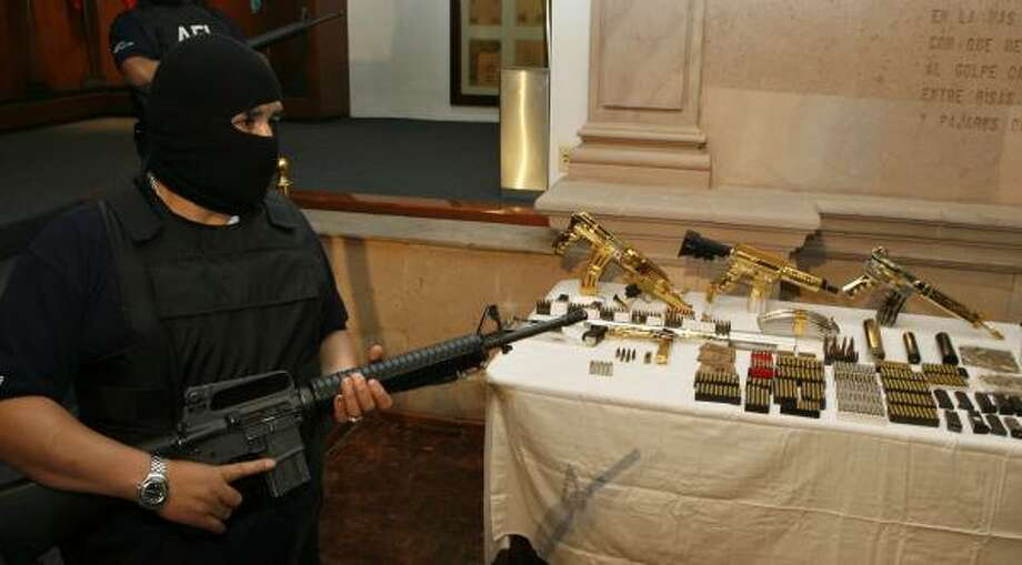Mexican federal police in Mexico City on Monday display weapons that were seized in a drug-trafficking bust. At least eight alleged members of the Gulf Cartel were detained in the operation. Photo: DARIO LOPEZ-MILLS, AP
