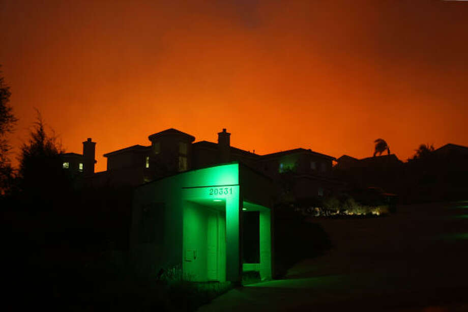 YORBA LINDA, CA - NOVEMBER 15:  Wildfire draws close to house on November 15, 2008 in Yorba Linda, California. Strong Santa Ana Winds are destroying hundreds of homes and charring thousands of acres around southern California. California Governor Arnold Schwarzenegger has declared states of emergency for the fires. Photo: David McNew, Getty Images