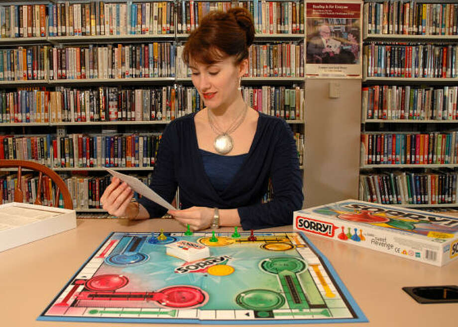 Sara Royall, South Branch Library assistant branch manager, reads the directions on a board game she has for the Family Game Night to be held at the library. Photo: David Hopper, For The Chronicle