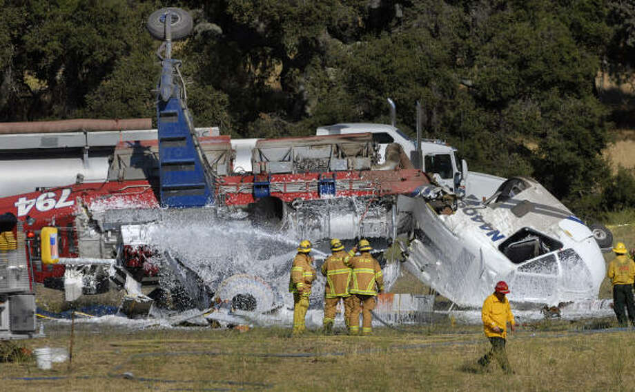 Firefighters spray foam on a helicopter that crashed near Los Olivos, Calif. on Sunday. Photo: Len Wood, AP
