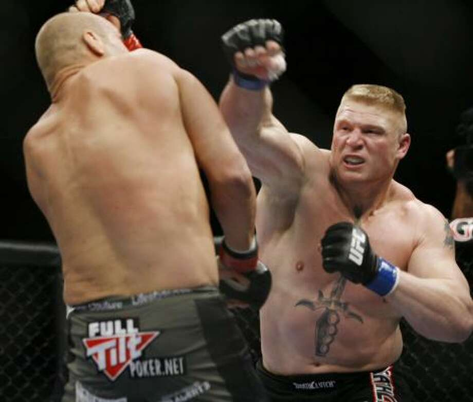 Brock Lesnar, right, was all over Randy Couture during their UFC world heavyweight championship match on Saturday in Las Vegas. Lesnar won by TKO in the second round. Photo: Eric Jamison, AP