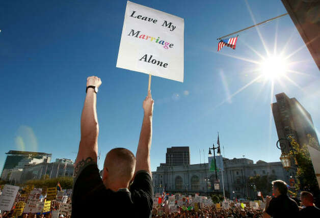"SAN FRANCISCOA supporter of gay marriage holds a sign saying ""Leave My Marriage Alone"" during a rally against the passing of Prop. 8 Saturday in California. Photo: Justin Sullivan, Getty Images"