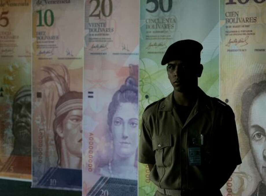 A security guard stands by oversized images of Venezuela's new currency, which enters circulation Jan. 1 Photo: HOWARD YANES, ASSOCIATED PRESS