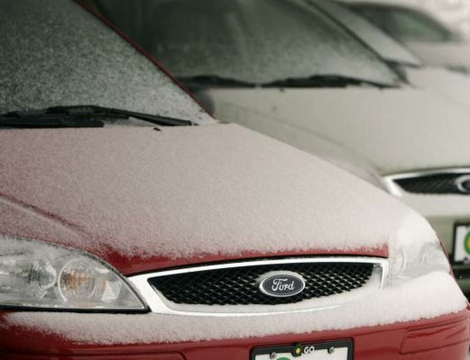 Snow covers unsold Ford Focus sedans on a lot in Littleton, Colo. Photo: David Zalubowski, ASSOCIATED PRESS