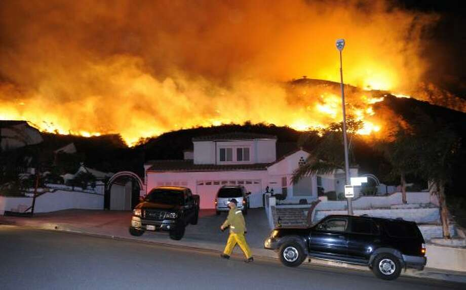 A firefighter walks up a street as a blaze burns toward homes during a wildfire that destroyed several homes Saturday, Nov. 15, 2008, in the Sylmar area of northern Los Angeles. Photo: Mark J. Terrill, AP