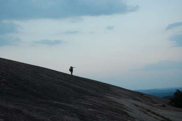 Hikers watch the sunset of Enchanted Rock.