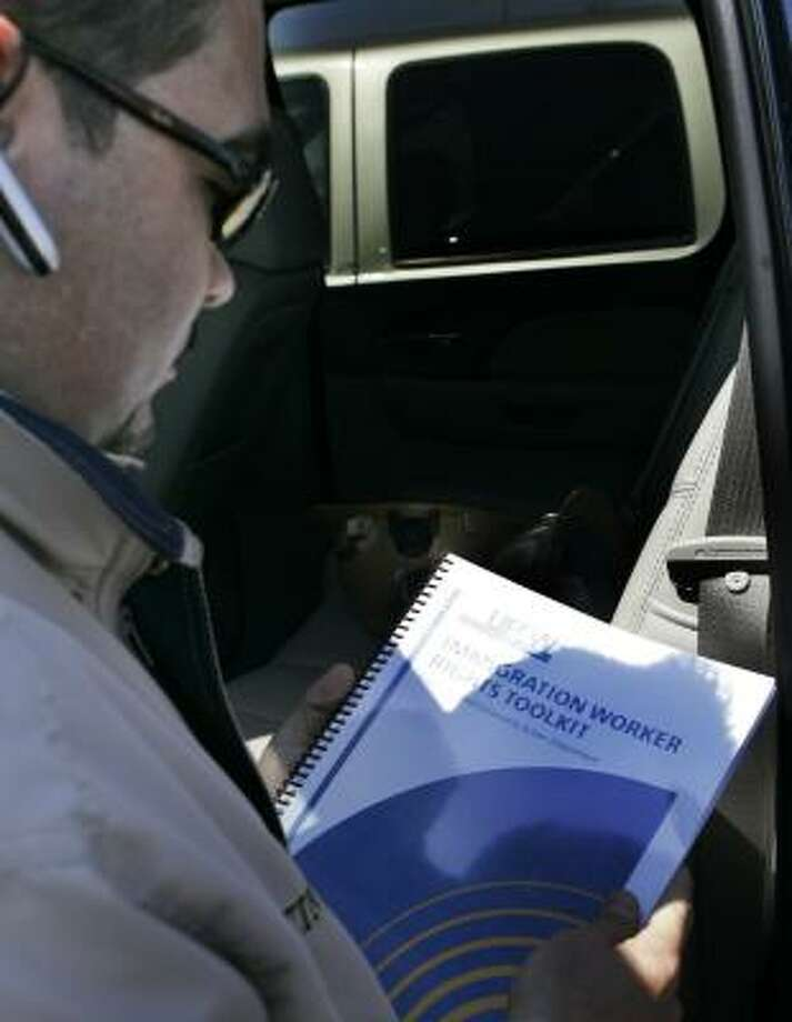 Martin Rosas examines a bilingual immigration rights kit in Dodge City, Kan. Illegal immigrants in meatpacking towns are preparing for possible arrest, following last year's raids. Photo: ORLIN WAGNER, ASSOCIATED PRESS