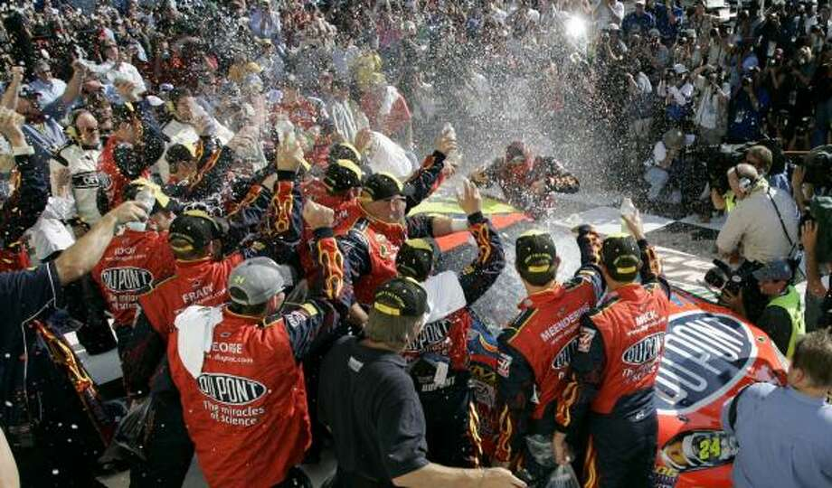 Jeff Gordon's crew showered him in celebration after winning his 77th career race. But some fans, angry that he passed Dale Earnhardt for sixth place on the all-time list, showered his car with beer cans in anger. Photo: Todd Bennett, AP