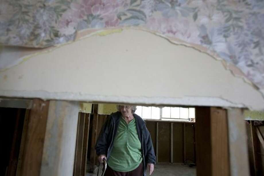 Viewed though an opened-up wall where drywall was removed, Kathryn Coleman, 86, walks out of a bedroom in her Shoreacres home. Hurricane Ike put more than three feet of standing water in her home. While waiting to rebuild, she's living in a trailer on the property she's owned for 28 years. Photo: Johnny Hanson, Chronicle