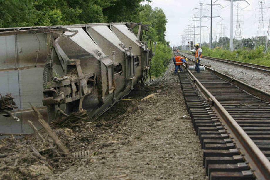 Union Pacific workers Korie Kinchen and Limpinski Davis examine tracks Tuesday at the site of the West U. train derailment. Photo: Melissa Phillip, Chronicle