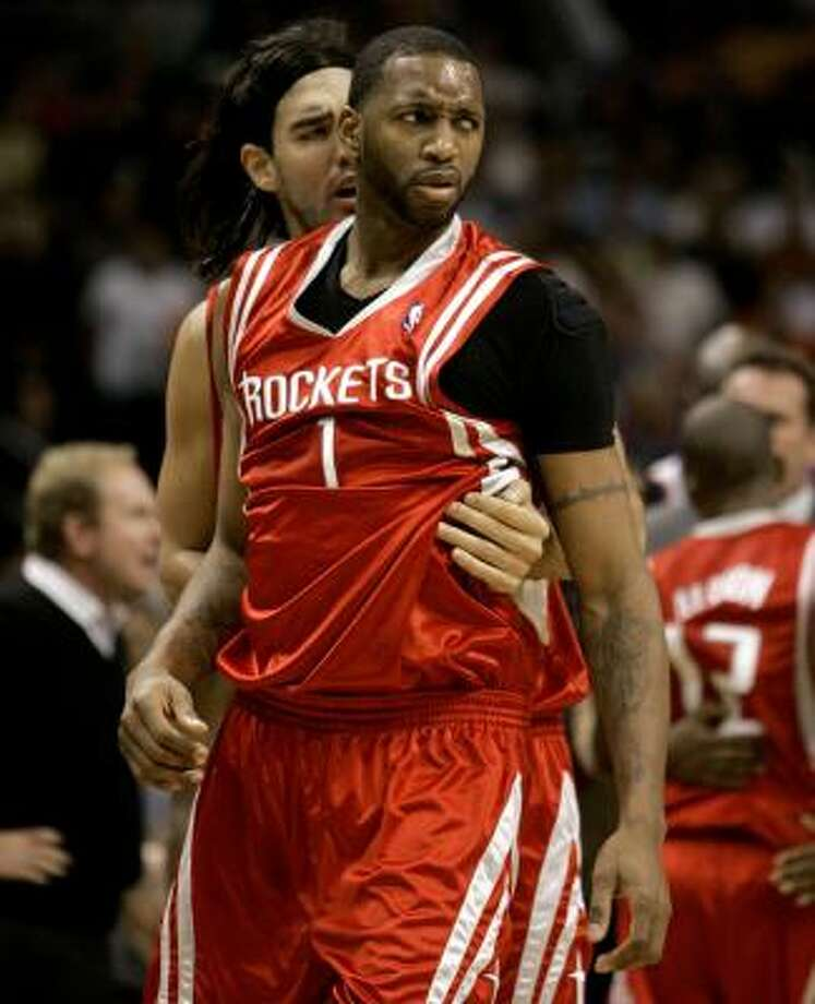 Rockets' Tracy McGrady is held back by teammate Luis Scola after a fight broke out against the Phoenix Suns. Photo: Matt York, AP