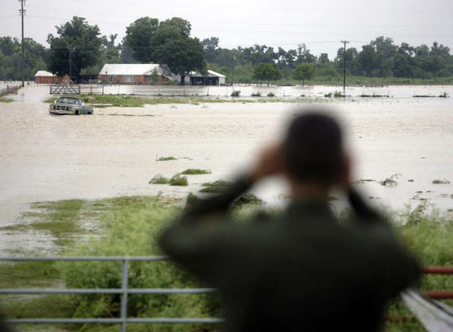 A Border Patrol agent looks for people needing assistance Saturday near D'Hanis, after heavy rains caused the Seco Creek to overflow its banks. Photo: William Luther, San Antonio Express-News