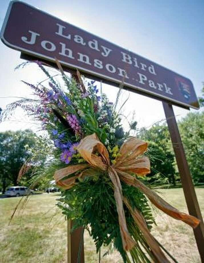 A floral arrangement stands near a sign at Lady Bird Johnson Park in Arlington, Va. Photo: MARK WILSON, GETTY IMAGES
