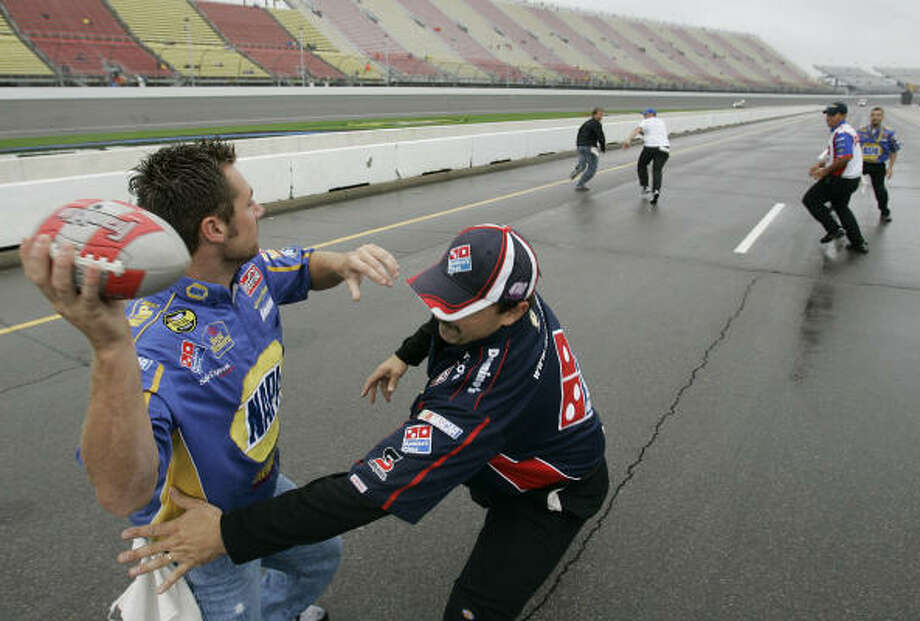 NASCAR pit crew members turned pit lane into a flag football field during the second straight rain delay at Michigan International Speedway. Photo: Paul Sancya, AP