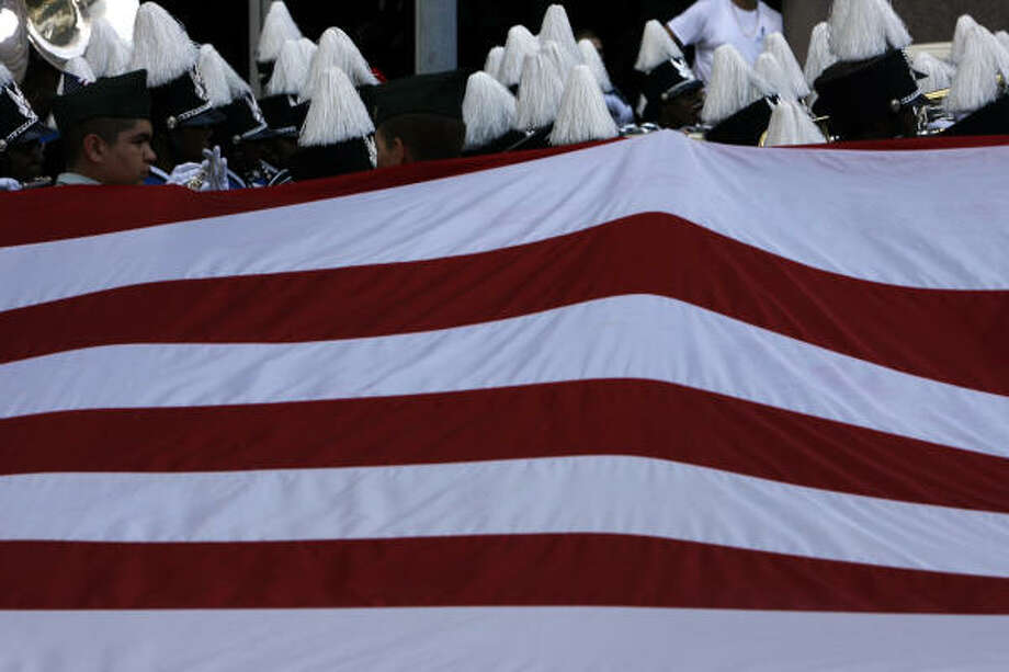 A band travels past the Reagan High School JROTC flag during the Veterans Day parade downtown Tuesday. Photo: Johnny Hanson, Chronicle