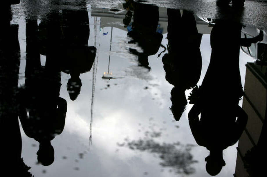 Sam Houston High School band members are reflected in a puddle of water after early morning rainfall as they prepare to for the Veterans Day parade downtown Tuesday. Photo: Johnny Hanson, Chronicle