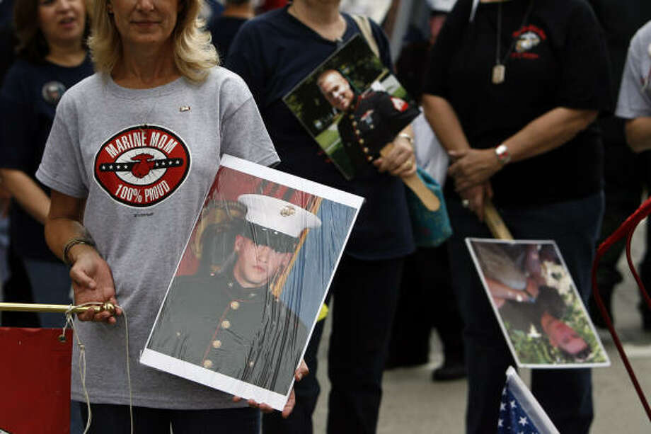 Gerri McWhirter, of Humble with Houston Marine Moms, holds a photo of her son Nathan Anderson, 23, who is serving with the Marines in Afghanistan, during the Veterans Day parade downtown Tuesday. Photo: Johnny Hanson, Chronicle