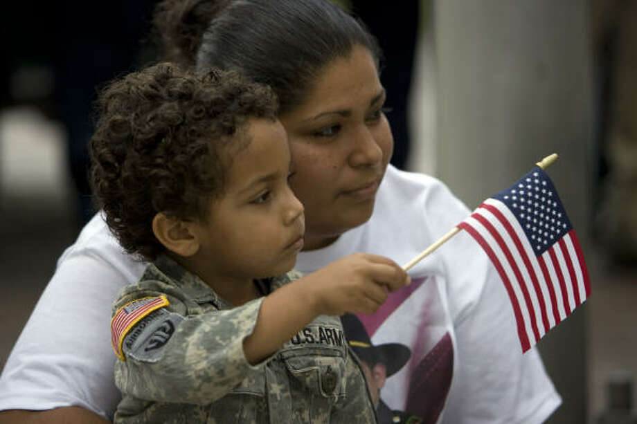 San Antonia DeLeon and her son Jacob, 3, watch the the Veterans Day parade downtown Tuesday. San Antonia's brother Johnny DeLeon served in Iraq. Photo: Johnny Hanson, Chronicle