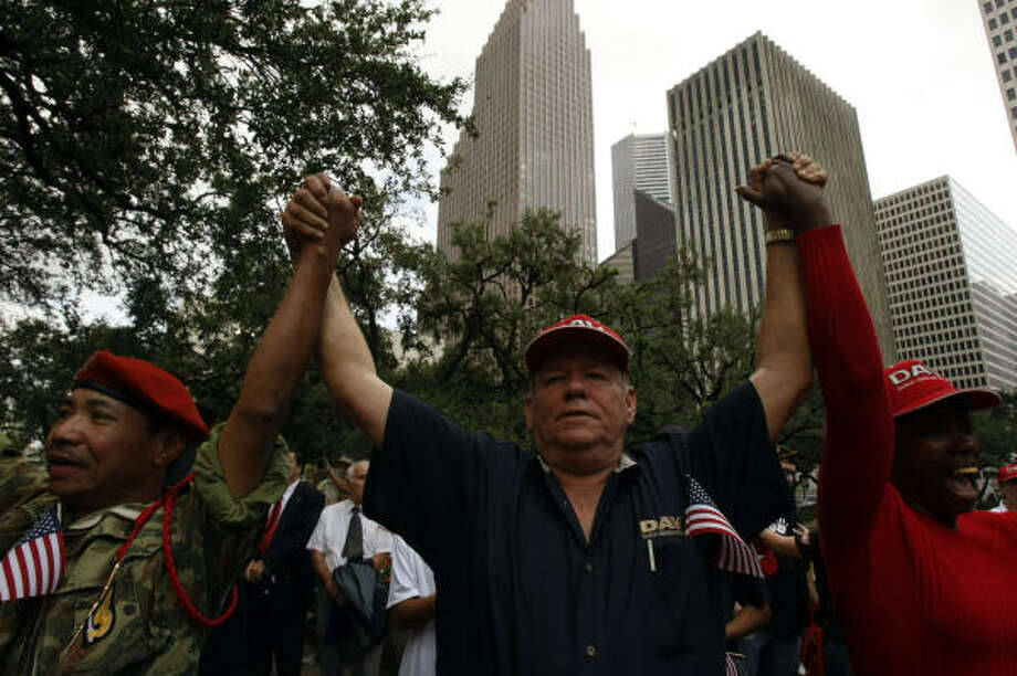 Stevent Le, a former Sgt. with the South Vietnamese Army, from left, Bob Douglass, who served in the Army in Vietnam and Carol Williams, who served in the Airforce in the 1980s, raise their arms during the playing of the song Proud to be an American during the commemoration ceremony outside City Hall. Photo: Johnny Hanson, Chronicle