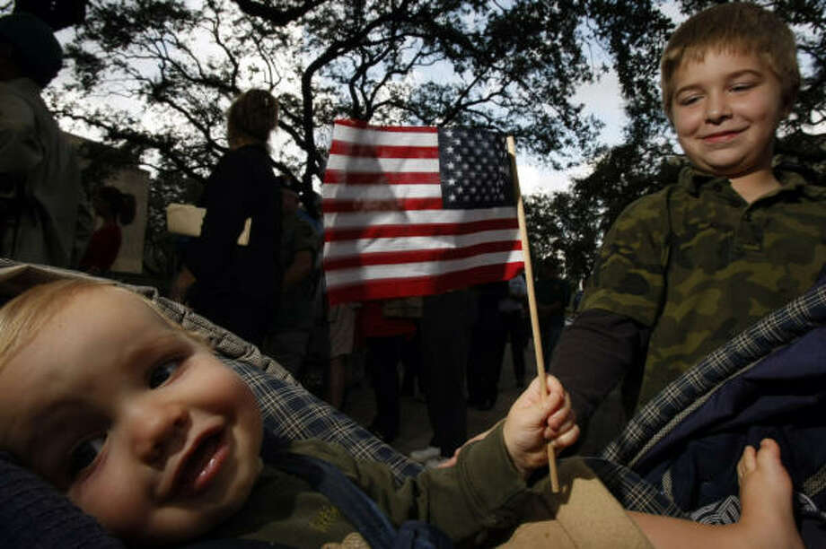 Simon McQuhae, 11 months, holds an American flag next to his brother, Ethan McQuhae, 7, during the commemoration ceremony outside City Hall. Photo: Johnny Hanson, Chronicle