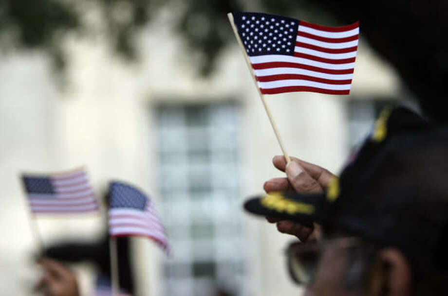 American flags are waved during the playing of Proud to be an American during the commemoration ceremony. Photo: Johnny Hanson, Chronicle