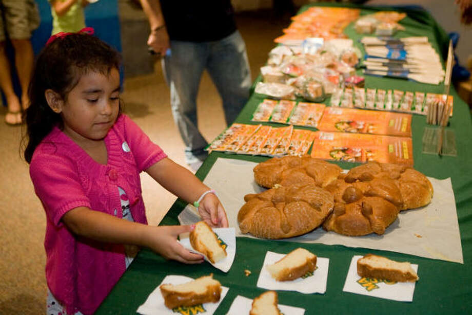 """DIA DE LOS MUERTOS:Liliana Muñiz, 5, grabs a piece of Pan de Muertos at Houston Children's Museum's Dia De Los Muertos celebration. Pan de Muertos or """"Bread of the Dead,"""" is a traditional sweetbread for the celebration. Photo: R. Clayton McKee, For The Chronicle"""