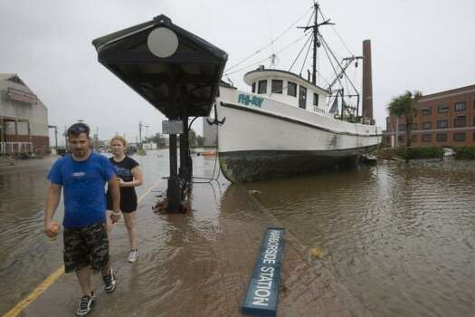 Von Johnson and Kristin Upp walk past a shrimp boat that was washed into a parking lot near The Strand. Photo: Brett Coomer, Chronicle
