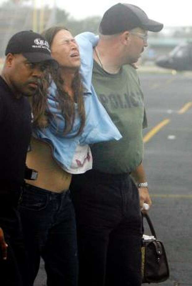 Rescuers help evacuee Sandra Pavelka, of Crystal Beach, after she arrives by helicopter at Texas City High School Sept. 13. Photo: Sharon Steinmann, Chronicle