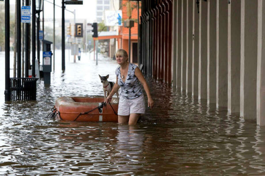 Leslie Sundell floats her dog on a life raft as she walks in The Strand district in Galveston on Saturday. Photo: Brett Coomer, AP