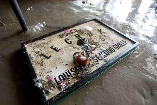 A sign from the Le Croy Bistro on The Strand lies in the muck. Photo: Brett Coomer, Houston Chronicle