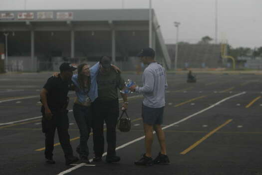 Sandra Pavelka, left, of Crystal Beach, is helped by rescue workers after arriving by Texas National Guard UH-60 helicopters at Texas City High School on Saturday. Photo: Sharon Steinmann, Chronicle