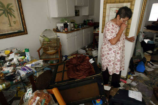 Sarah Bynum walks through her flooded apartment in a retirement community on 61st Street in Galveston. Photo: Johnny Hanson, Chronicle