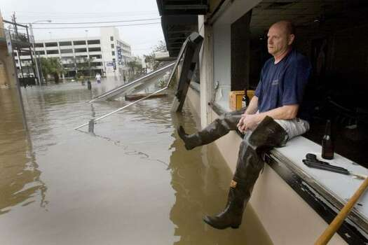 Brian Merrell sits on the window ledge of Rudy and Paco Restaurant. He was keeping watch over the business that lost it windows and was flooded. Photo: Brett Coomer, Chronicle
