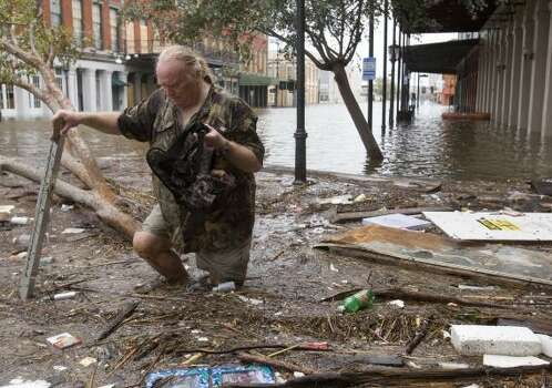 Tom LeCroy walks through debris strewn in The Strand that suffered flooding in the aftermath of Hurricane Ike on Sept. 13. Photo: Brett Coomer, Chronicle