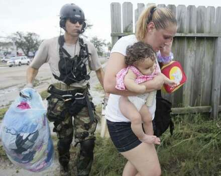 A National Guard member escorts evacuee Ellie Cox and her 6-month-old daughter, Jazya, to a waiting helicopter in Galveston Sept. 13. Photo: Melissa Phillip, Chronicle