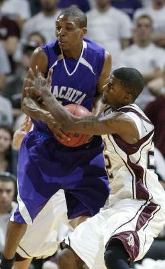 Ouachita Baptist's Brandon Rose, left, wrestles Texas A&M's Dominique Kirk for a rebound in College Station. Photo: PAUL ZOELLER, AP