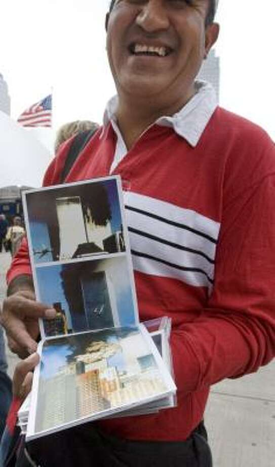 An unidentified vendor markets a photo booklet at the World Trade Center site. It's illegal, but enforcement is spotty. Photo: MARK LENNIHAN, ASSOCIATED PRESS