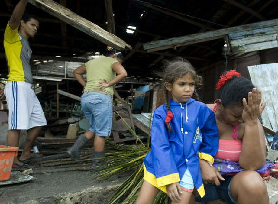 A woman and her family try to pick up the pieces after their house was destroyed by Hurricane Paloma. Photo: ADALBERTO ROQUE, AFP/Getty Images