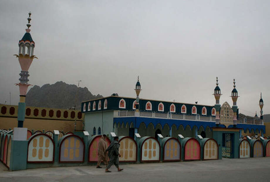 Afghans walk near the mosque on the outskirts of Kandahar that once was part of the compound of Taliban leader Mullah Omar. U.S. Special Forces units have been living and training at the compound since soon after the fall of the Taliban. Photo: RAFIQ MAQBOOL, AP