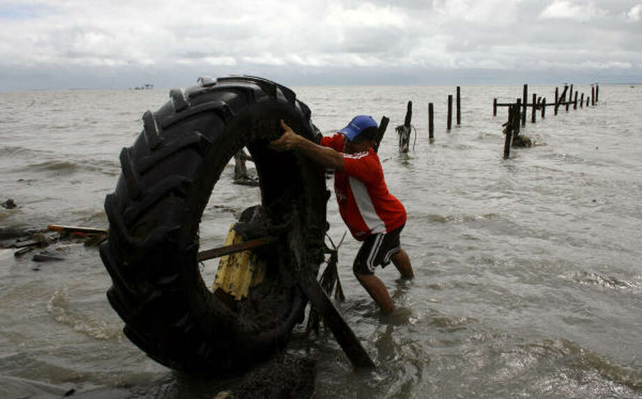 A man pulls a tire out of the water in the aftermath of Hurricane Paloma in Santa Cruz del Sur, Cuba, Sunday. Photo: Javier Galeano, AP