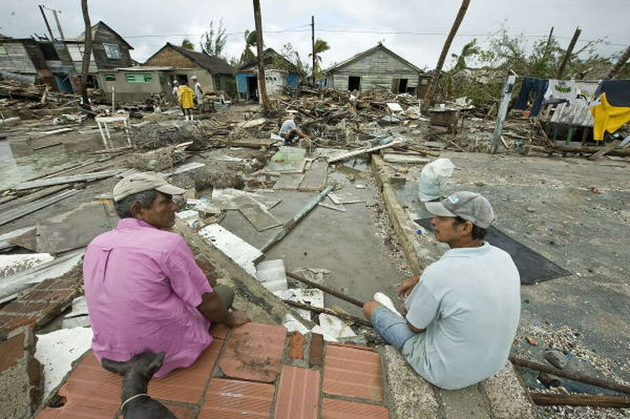 Two residents rest in the remains of their destroyed house Sunday after the passage of Hurricane Paloma over the town of Santa Cruz del Sur. Photo: ADALBERTO ROQUE, AFP/Getty Images