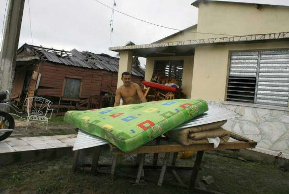 A man recovers his belongings in Santa Cruz del Sur. Photo: Javier Galeano, AP