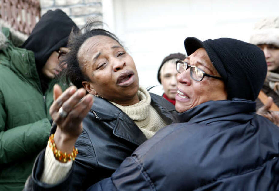 Distraught family members try to comfort each other at the scene of a house fire that killed nine on Thursday in the Bronx. Photo: Jason DeCrow, AP